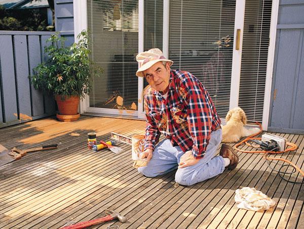 Spring deck maintenance checklist - Homeowner laboring on refinishing wood deck