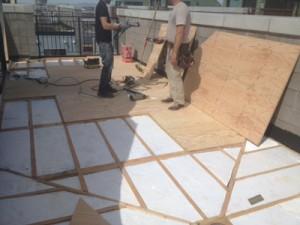 Preparing the roof deck substrate for the application of Duradek vinyl.