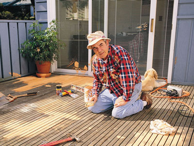 Man on knees working on redoing deck.