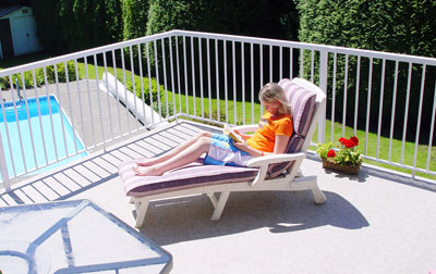 Girl lounging and reading on a Duradek deck.